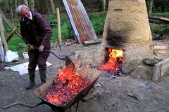 Removing hot charcoal from the bottom of the furnace.