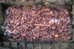 The ore being roasted in a wood-fuelled hearth to convert to the oxide [maghemite, Fe2O3], a magnetic form that is attracted to a magnet; a useful characteristic for checking that pieces are really iron ore. When roasted, the ore changes colour from grey to reddish-purple.